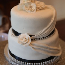 Tiered Summer Wedding Cake with Black Ribbon and Cascading fabric with Rose Accents