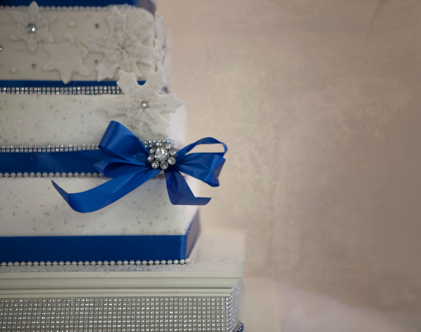 White Winter Wedding Cake | Square Tiered Wedding Cake with Cobalt Blue Ribbon and Powdered Sugar Snow